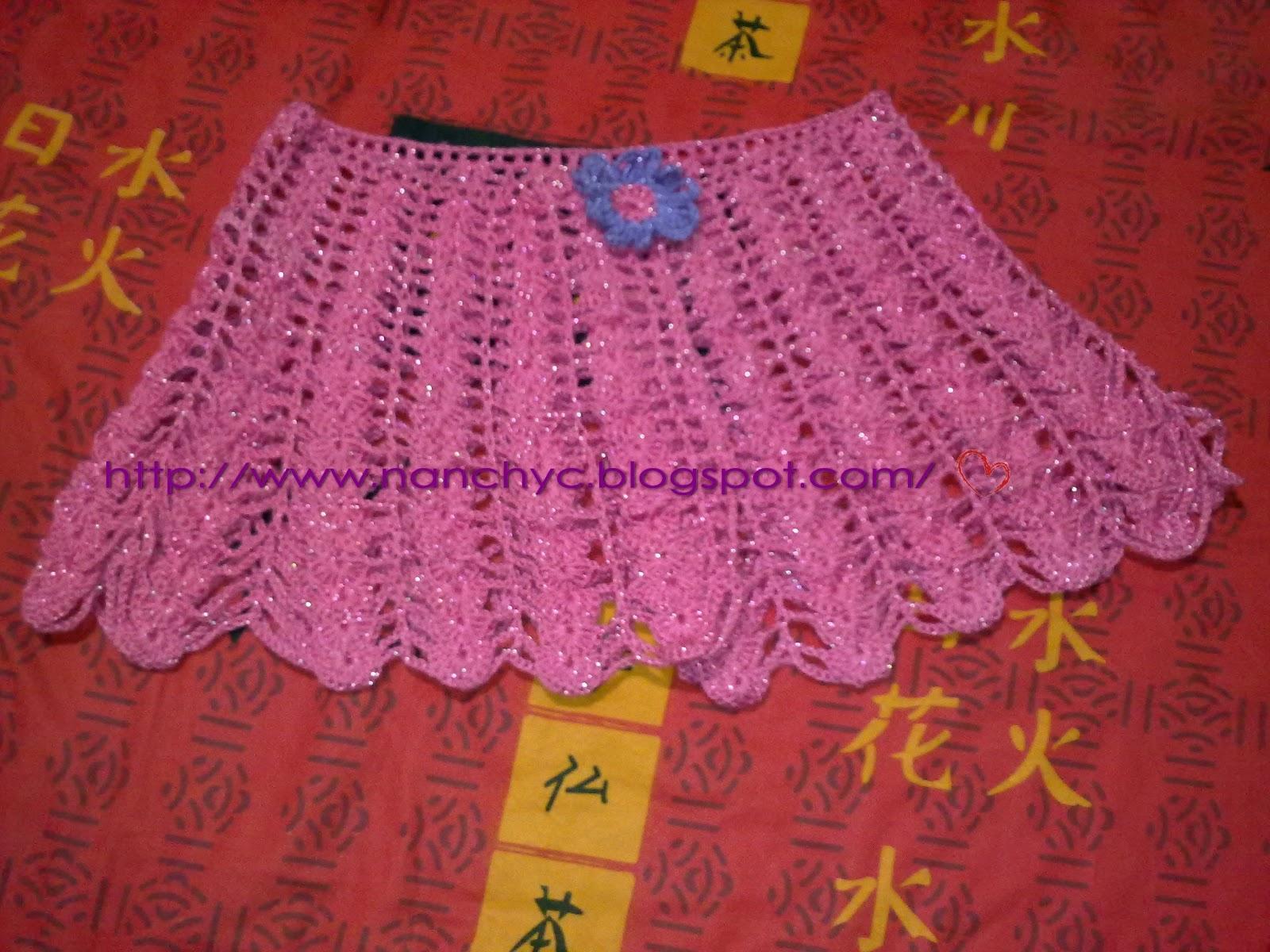 Chal tejido en crochet en lana fucsia y con broche de flor lila .
