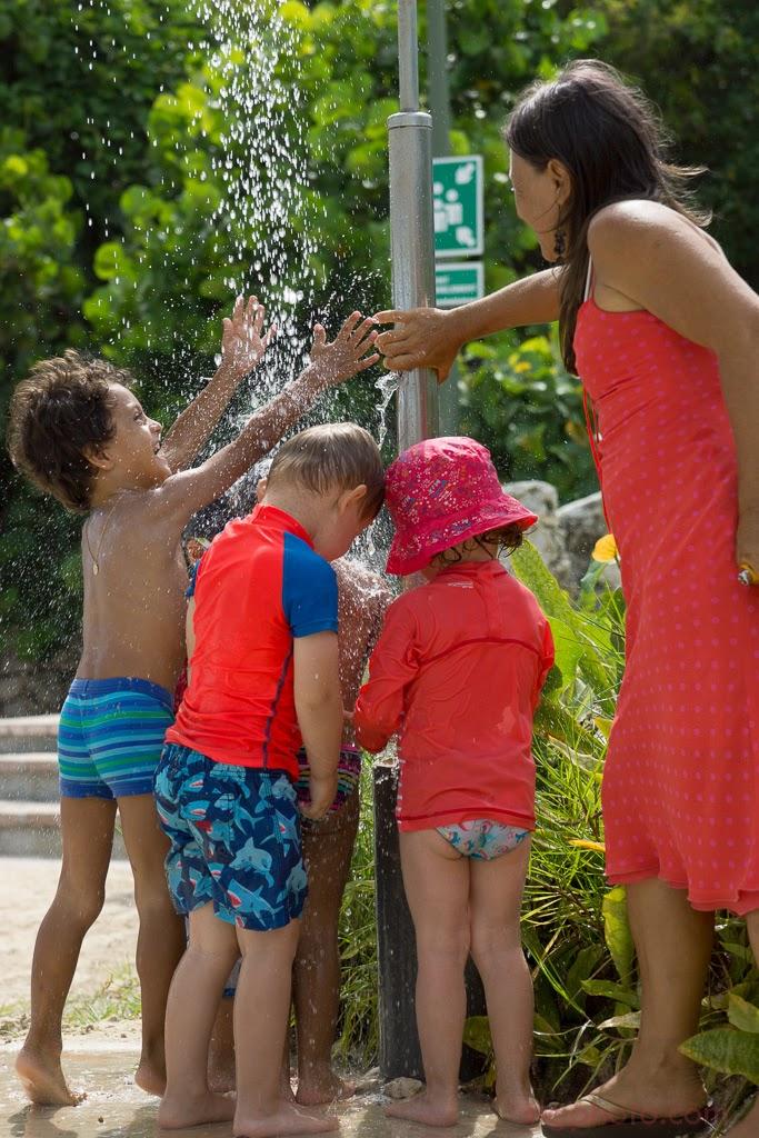 Les enfants se rafraîchissent sous la douche de plage