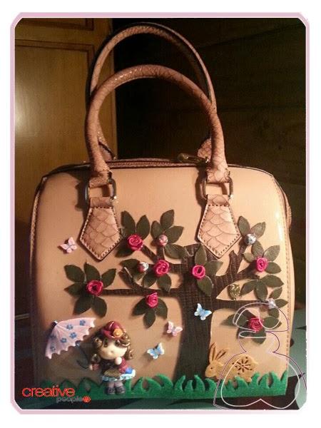 Bolso de mano en piel en tono camel decorado a mano por Sylvia Lopez Morant.
