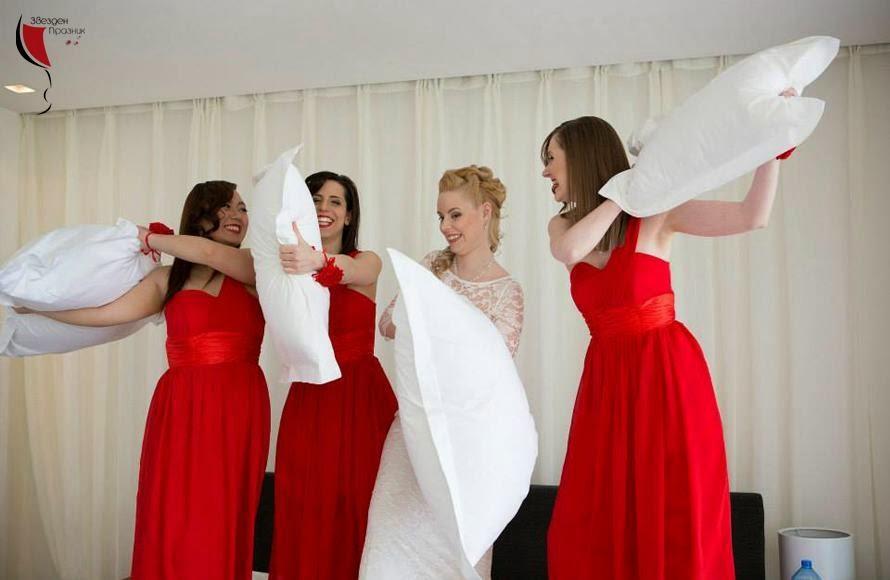 шаферки с ярко червени рокли и красивата булка бой с възглавници