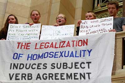Neatly handmade banner hanging from a Capitol railing revised to read THE LEGALIZATION OF HOMOSEXUALITY INDUCES SUBJECT VERB AGREEMENT