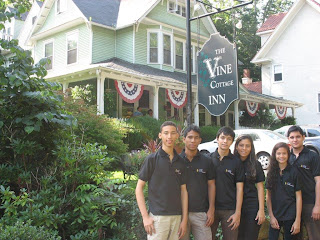 group of 6 guests standing in front of Vine Cottage Inn sign with Inn in the background