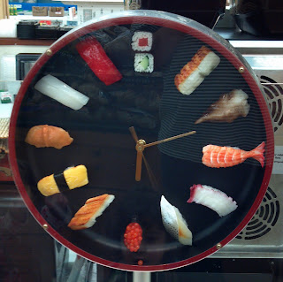 clock with pieces of sushi at each horu