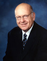Bald, bespectacled middle aged white man wearing a suit and tie.