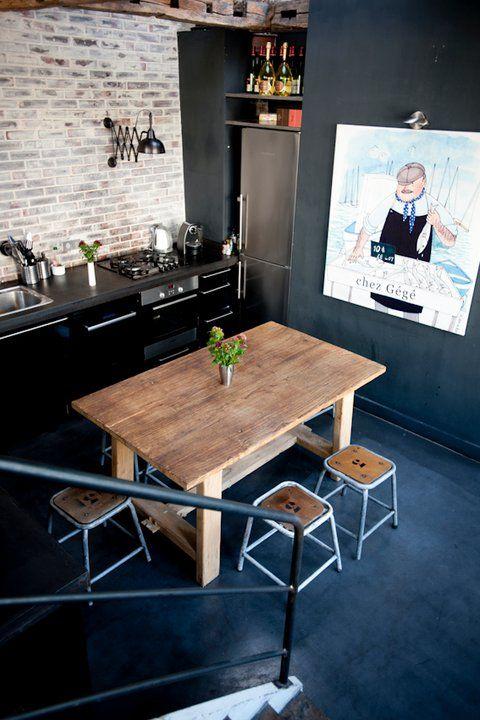 et mørkt moderne køkken med rustikke møbler og stort kunst