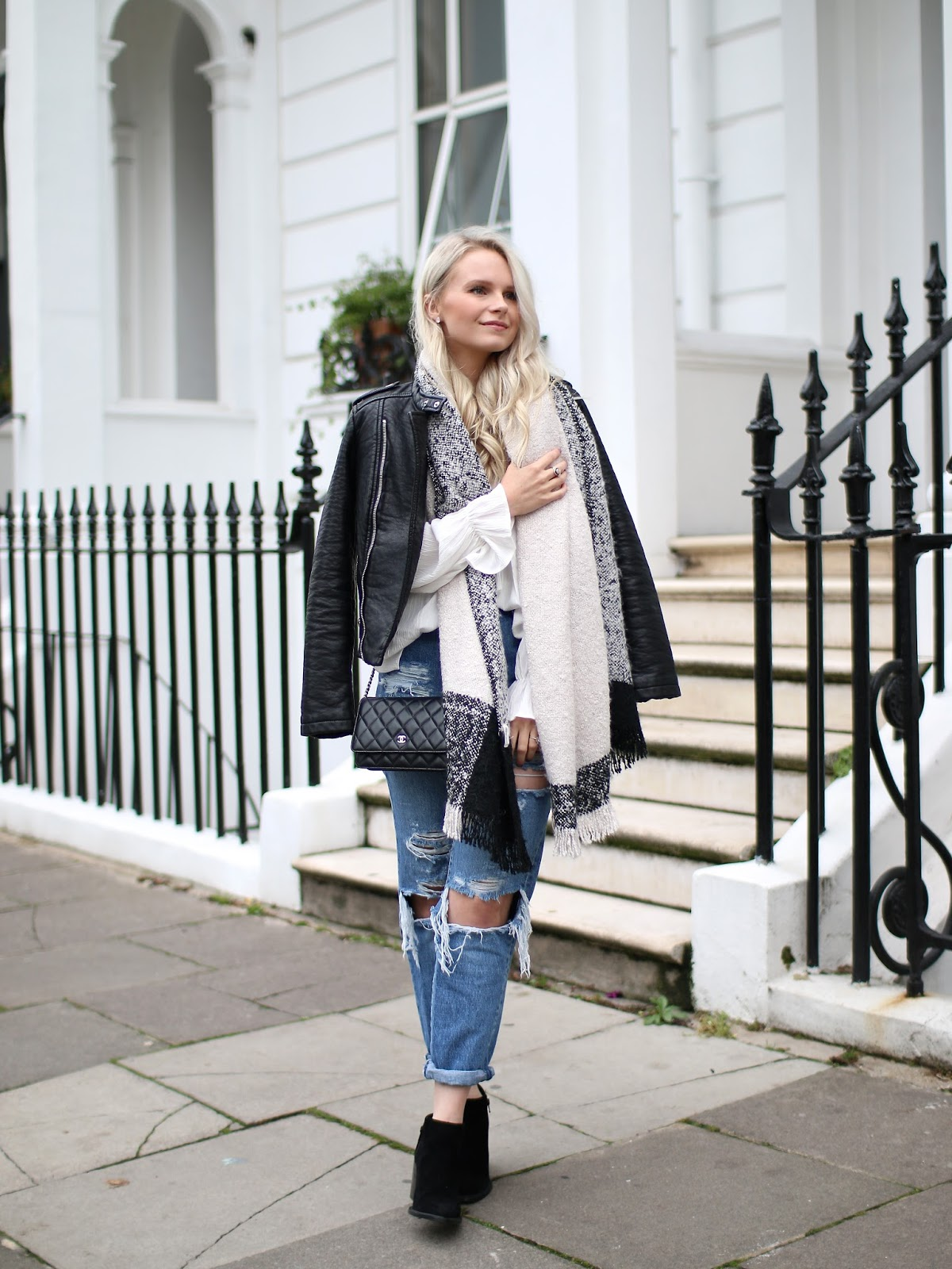 a blonde women with loose curls in her hair standing on the sidewalk in notting hill wearing a warm leather jacket and river island scarf