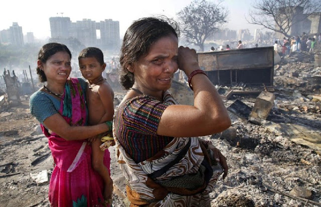 Women cry after fire broke at slums in Kadivali area
