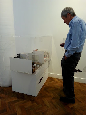 Man looking at a miniature scene exhibited in a gallery.