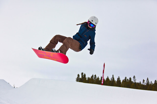 A girl on a snowboard launching out of the half pipe in Breckenridge, Colorado.