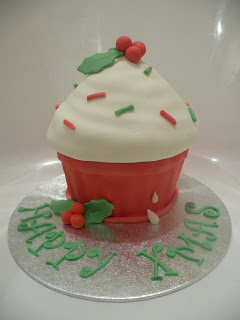 Happy X mas wishes written on Christmas giant cupcake decorated with Christmas leaves photo