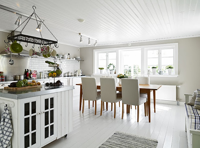 White kitchen swedish cottage wood table high back chairs painted wood floor white subway tile backsplash