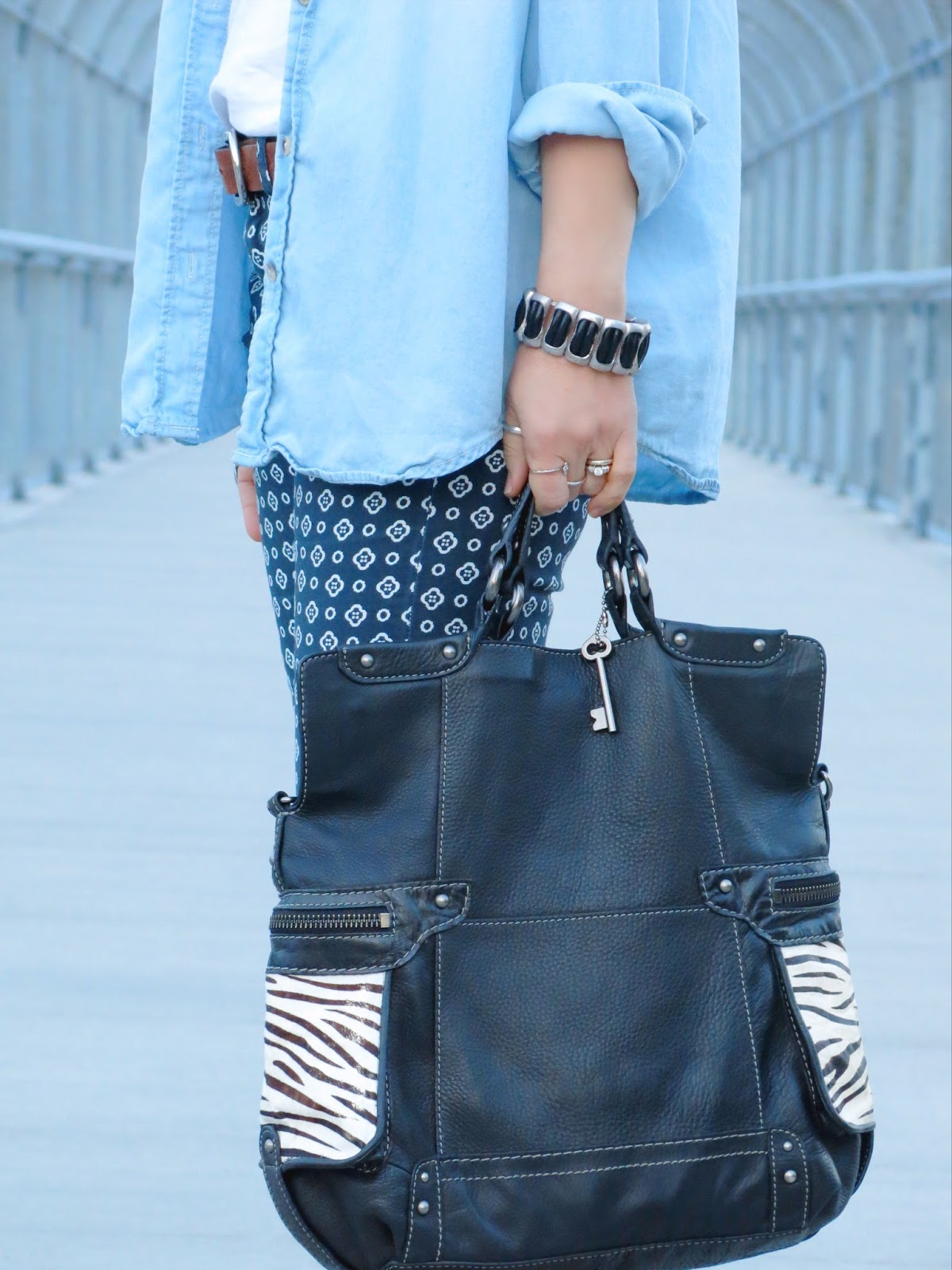 chambray shirt, printed pants, zebra-printed Fossil bag, metal and leather bracelet