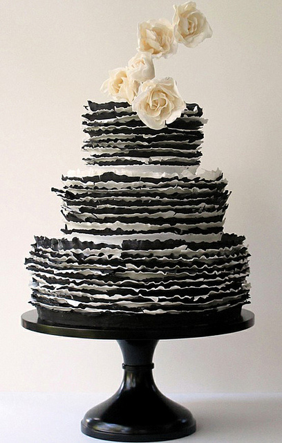 Set over three round tiers a black and white striped ruffle cake with cream