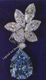 Earring with a rare blue 6.61-carat diamond suspended from a cluster of white navettes