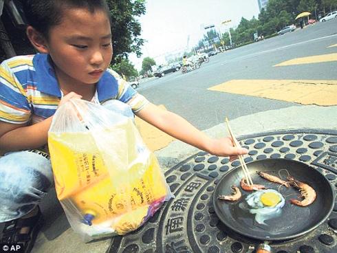 Seorang kanak-kanak menggoreng telur dan udang di tepi jalan ketika tengah hari dalam timur wilayah Shandong, China.