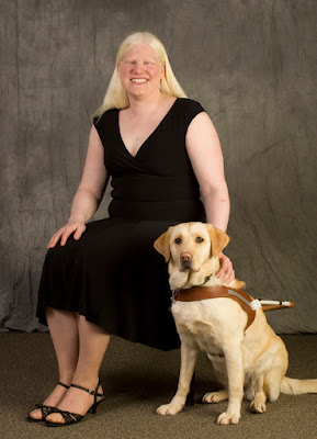 Nicole smiles (wearing a black dress and shoes) with Picassa (yellow Lab in harness) on graduation day on the Oregon campus.