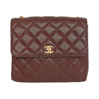 1990's vintage burgundy Chanel flap bag with gold front closure.