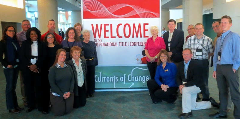 a group of conference attendees pose for a picture beside a welcome banner.