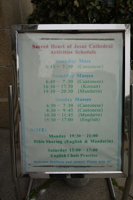 sign showing schedule of church services and events with only a few being in English
