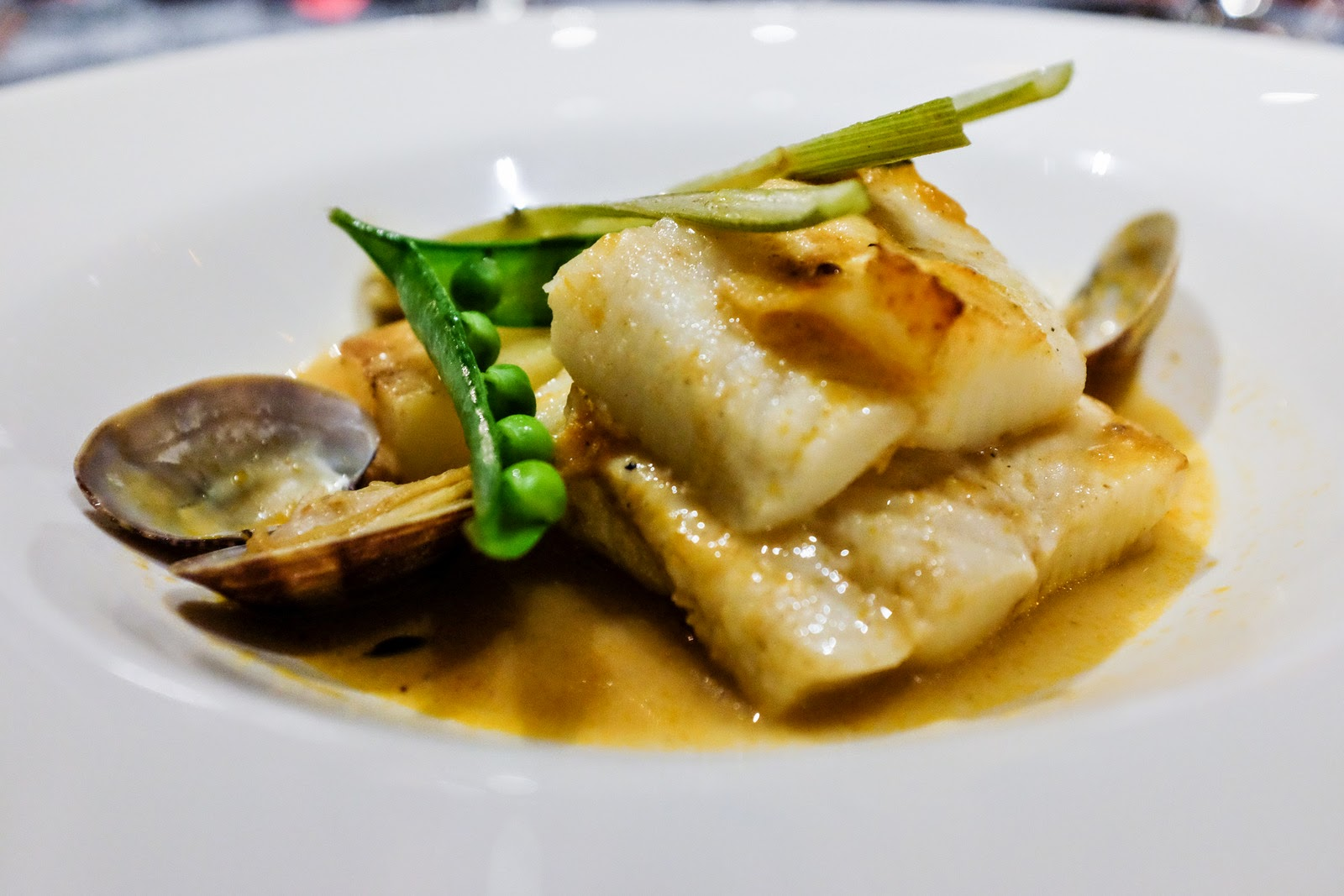 Slow-poached halibut, flaky & fresh-tasting, in a briny broth that ...