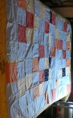 another photo of the quilt top, looking from a standing perspective at it laid out on the lounge floor