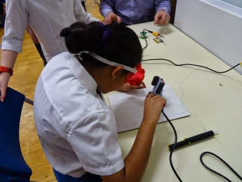A girl soldering a DIY Gamer Kit