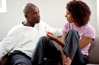 Couple sitting on the couch emotionally connecting through conversation.