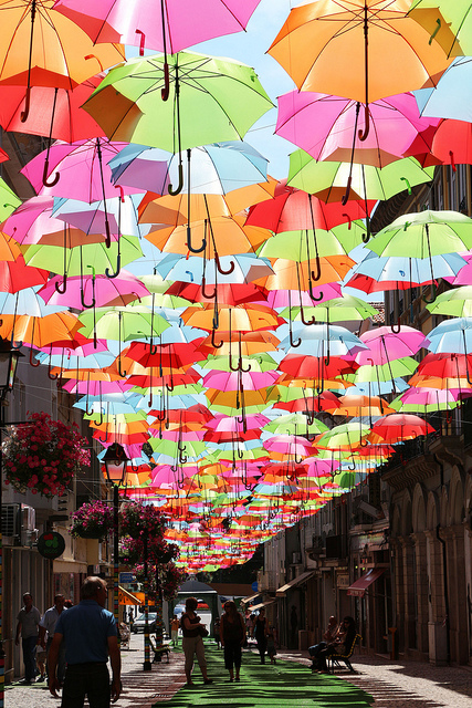 umbrellas covering the sky of a street in portugal in july