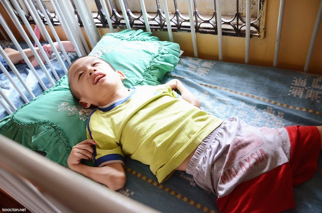 A child laying in bed, confined to it the rest of his life