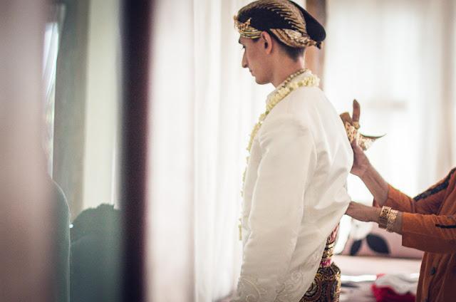 pengantin pria sedang menyematkan keris dibantu oleh perias dalam persiapan pernikahan adat jawa di jogja