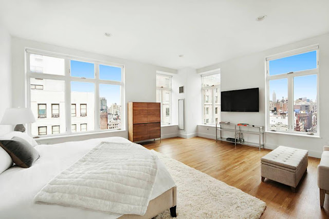 Modern bedroom in a NYC penthouse with wood floor, shag rug and views of the city