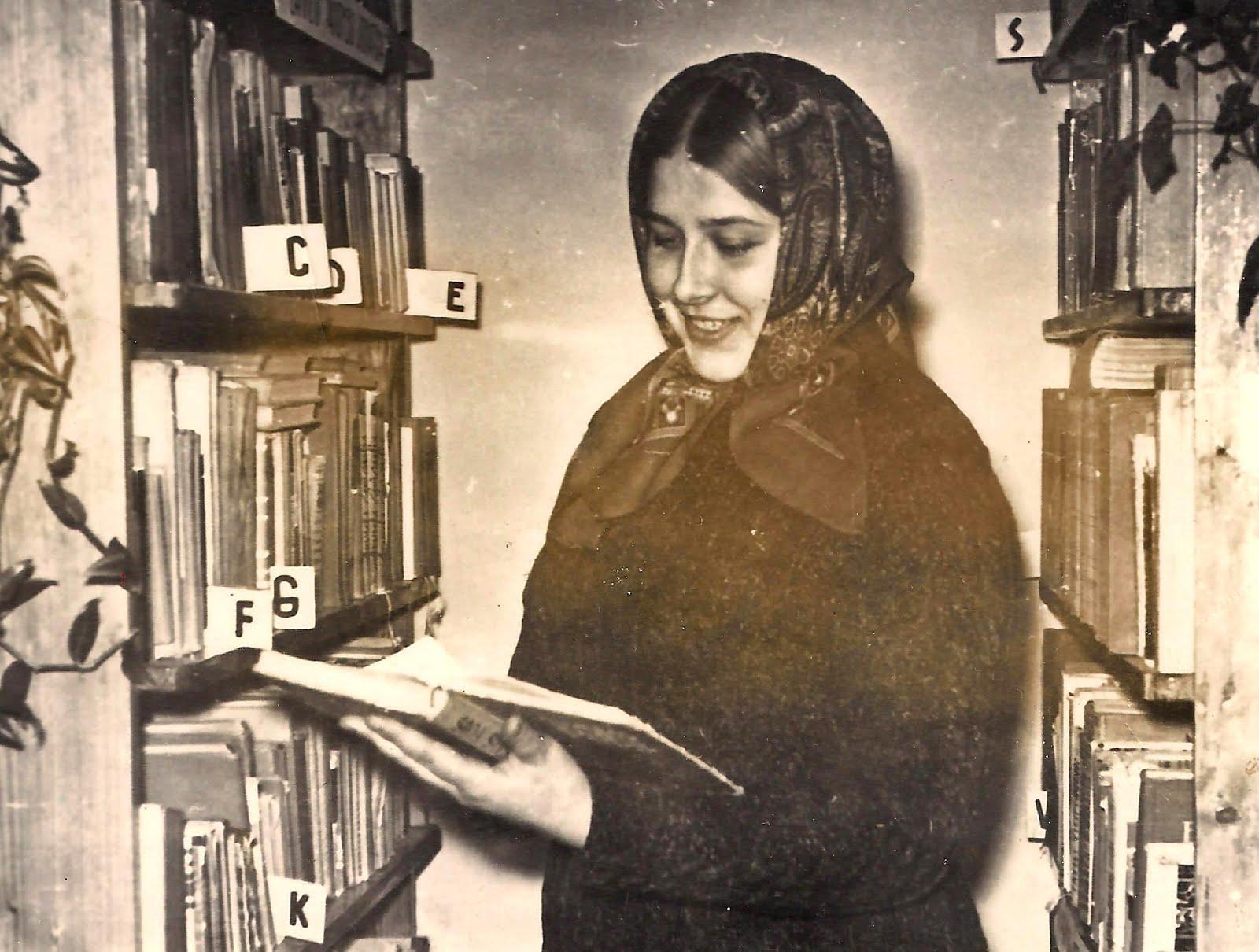 Lasītāja starp bibliotēkas plauktiem
