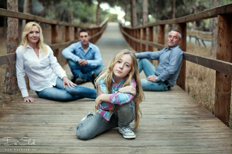 familia posando en una pasarela de madera vestida con vaqueros azules