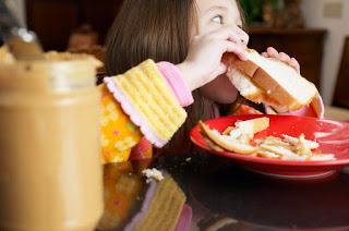 Girl eating a peanut butter sandwich MP900422681