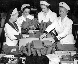 Washington, DC, June 1942—These volunteer production workers of the American Red Cross prepared over 300,000 kits containing small articles for the comfort of the men sailing to foreign ports. The kits contained soap, writing materials, shoe laces, playing cards, a polishing cloth, and a paperback novel. Photo by F. Fusco