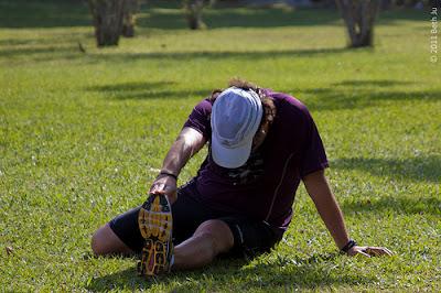 Homem fazendo alongamento na grama