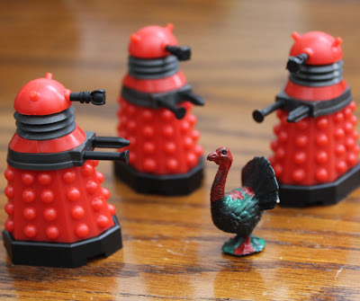 doctor who dalek toys have guns pointed at a turkey figure