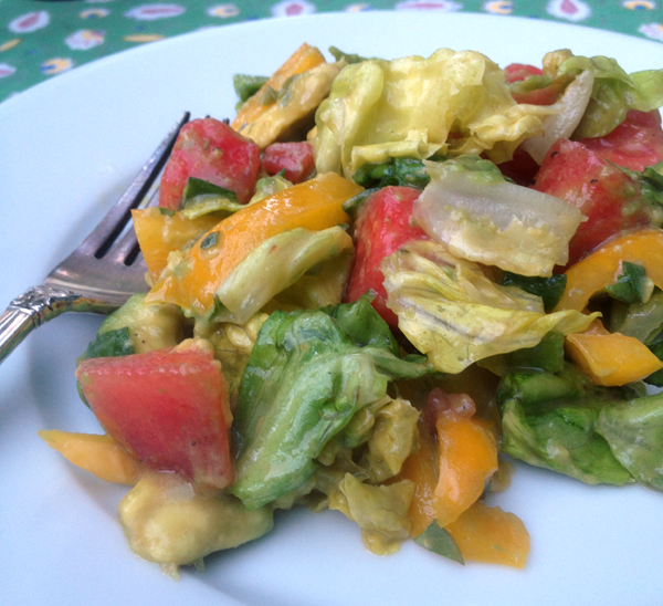 Single serving of Avocado and Watermelon Salad on a white plate served al fresco.
