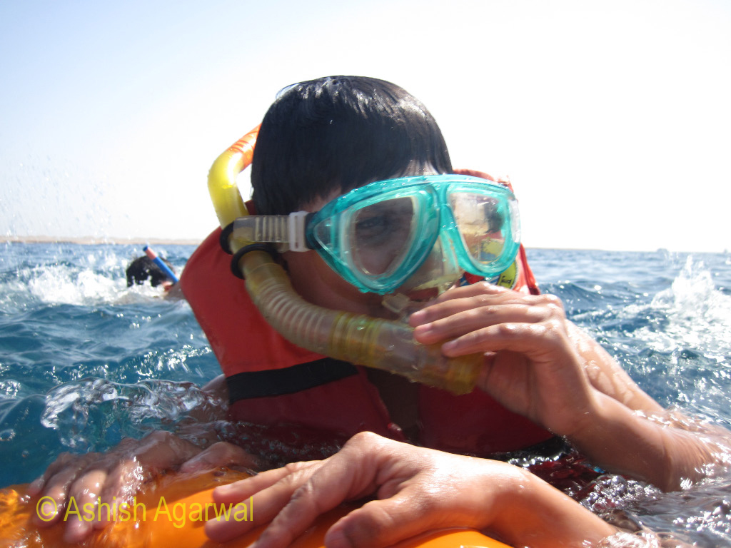 Snorkeling mask, air pipe and life vest at the water surface at Sharm el Sheikh