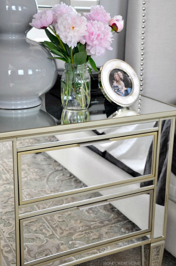 neutral master bedroom, mirrored nightstand with pink flowers and gray lamp
