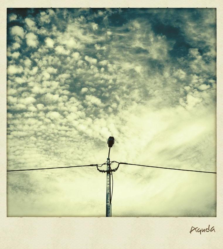 Foto a simular a Polaroid com um céu nublado e um poste de electricidade no centro da imagem