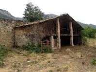 La pallissa del mas Viladomat al costat d'alts murs de pedra seca