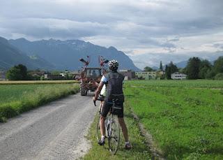 Cyclist yields to farm equipment along a gravel path, Liechtenstein.