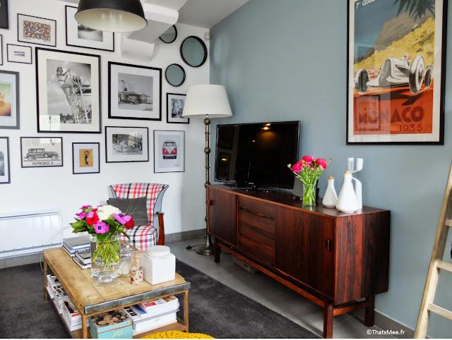 meuble Tv scandinave bois foncé Allt* Paris 17, déco mur de cadres photos, table basse bois l'Etrier brocante, pouf maille couleur jauen moutarde