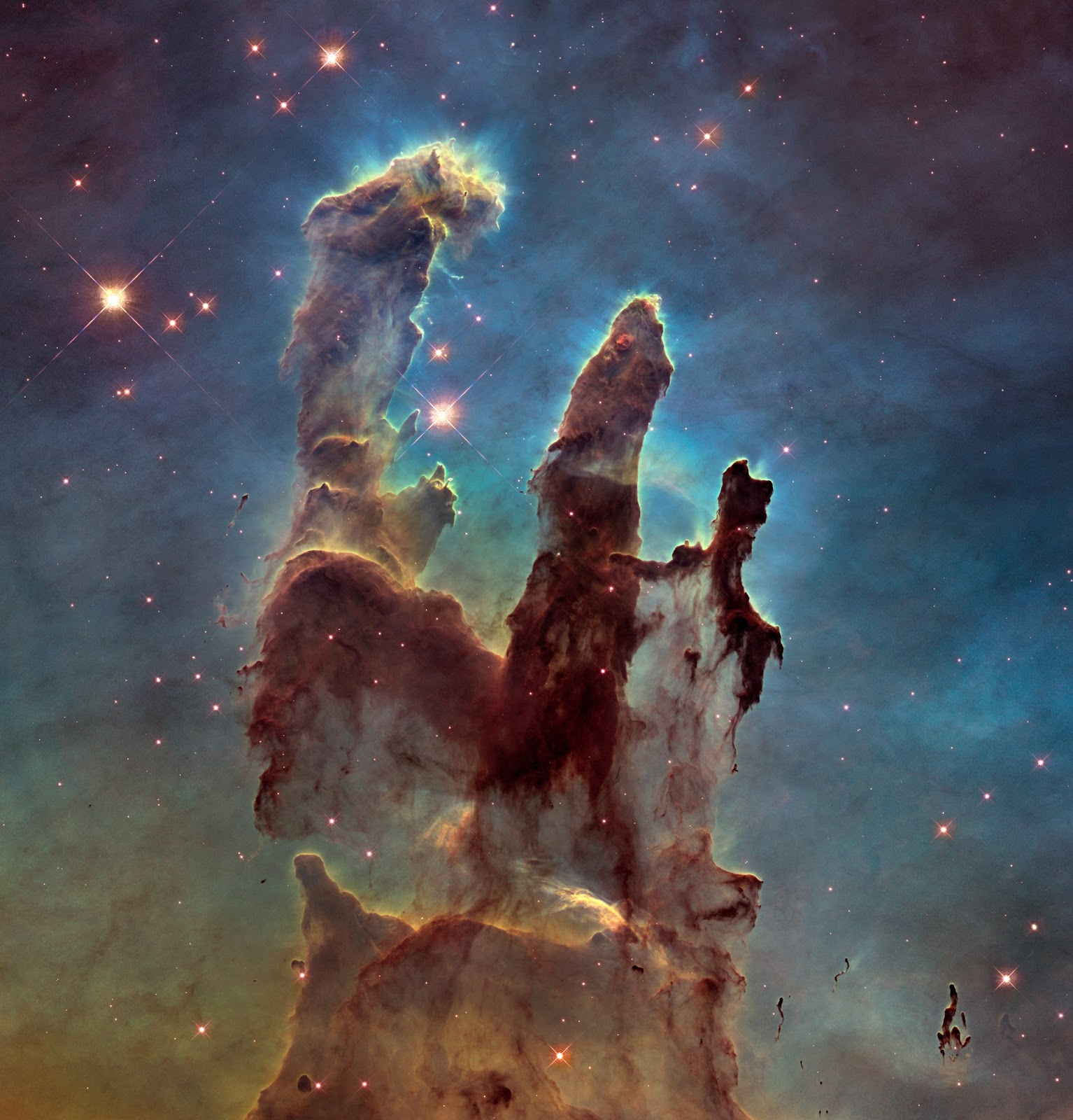 New view of the Pillars of Creation New view of the Pillars of Creation   The NASA/ESA Hubble Space Telescope has revisited one of its most iconic and popular images: the Eagle Nebula's Pillars of Creation. This image shows the pillars as seen in visible light, capturing the multi-coloured glow of gas clouds, wispy tendrils of dark cosmic dust, and the rust-coloured elephants' trunks of the nebula's famous pillars.  The dust and gas in the pillars is seared by the intense radiation from young stars and eroded by strong winds from massive nearby stars. With these new images comes better contrast and a clearer view for astronomers to study how the structure of the pillars is changing over time.  Image Credit: NASA, ESA/Hubble and the Hubble Heritage Team Explanation from: http://www.spacetelescope.org/images/heic1501a/