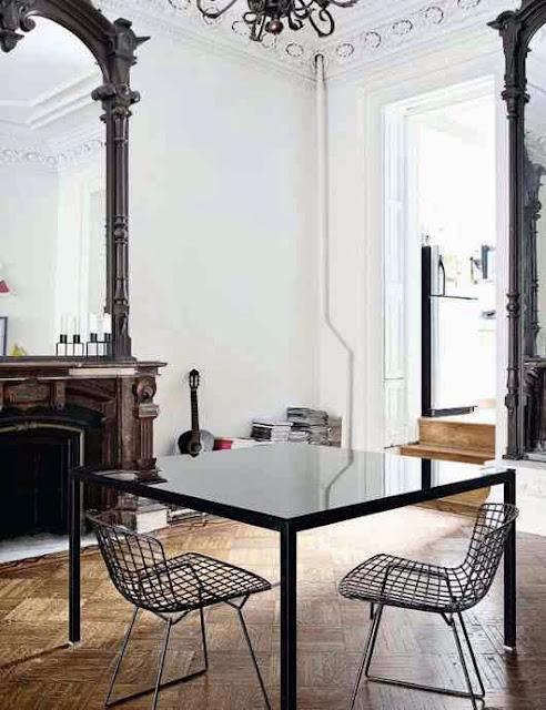 Czarne druciane krzesła przy stole w salonie z wysokim sufitem