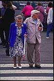 Hombre y mujer de avanzada edad cruzando la calle por un paso de peatones.