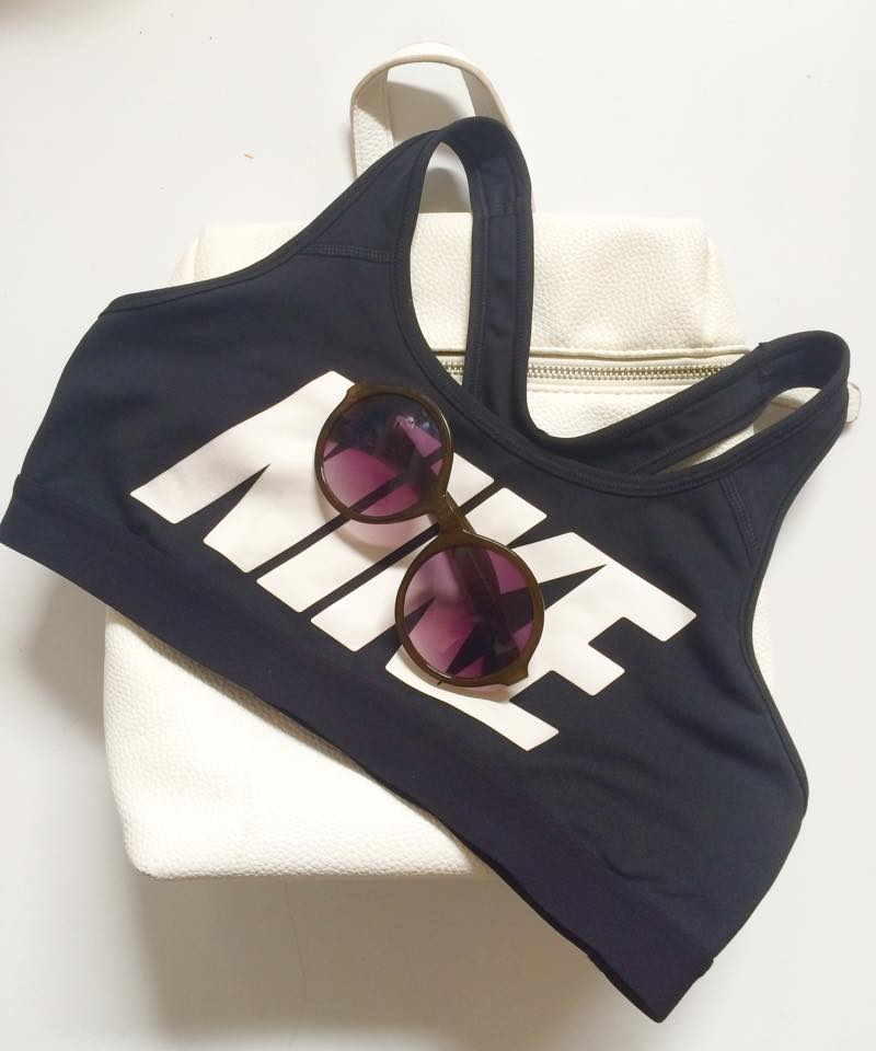 Young Hungry Free white backpack, Nike sports bra, Urban Outfitters circle sunglasses