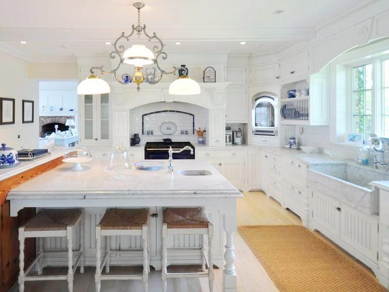 Kitchen with white cabinets, light wood floor, a white island surround by white stools with sea grass chairs, a farmhouse sink, a chandelier and a sea grass rug
