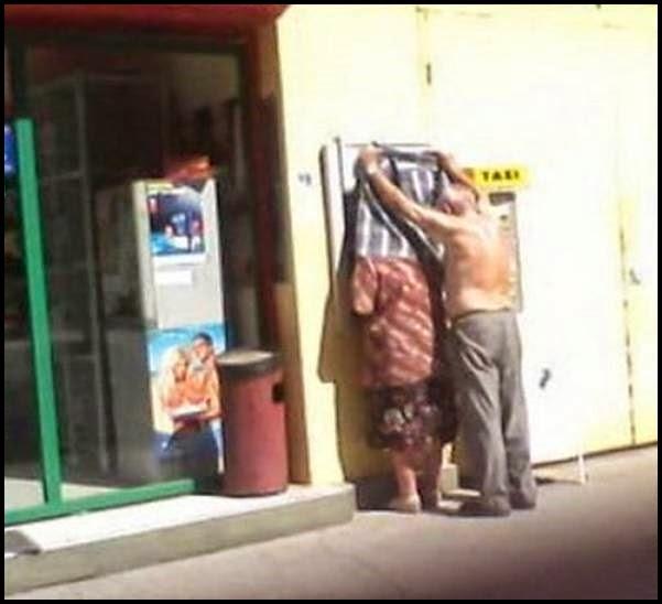 Hombre cubriendo con camisa a mujer en el cajero.